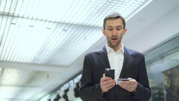 Sikeres üzletember csinál fizetés, hitelkártya és okostelefon 4k
