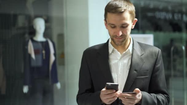 Sikeres üzletember tartja a kártyát kap, és nagyszerű hír a smartphone 4k