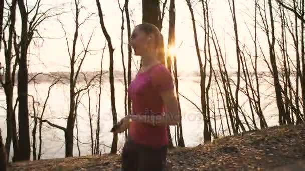 hübsches Mädchen, das im Park spazieren geht und die Musik in Kopfhörer 4k hört