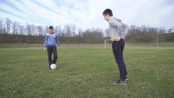 Dva chlapci hrají s míčem na stadionu v rozlišení 4k
