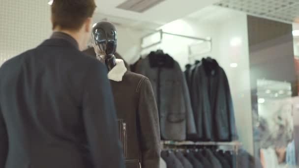 Elegantní bohatý muž v obleku, výběr oblečení v obchod s oblečením