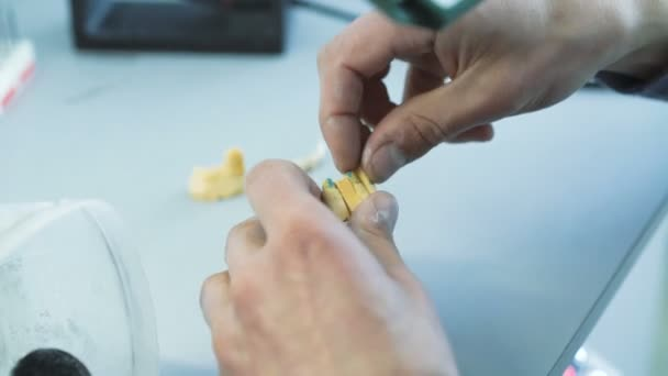Closeup of making teeth crowns in dental lab in 4k
