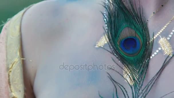 Portrait of image of peahen looking to camera and tickling with feather. Slowly