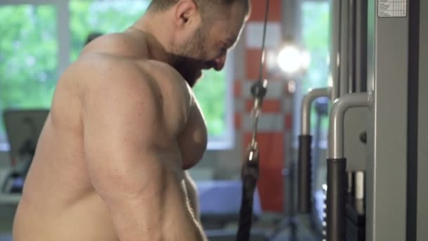 Close-up of strong handsome bodybuilder training triceps in the gym