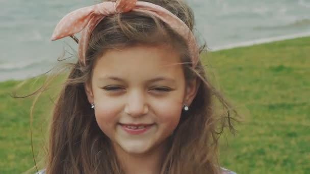 Unbekümmert lächelt das kleine Mädchen in die Kamera am Pool. langsam