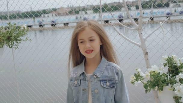 Chytrý malý ženský model s dlouhými vlasy, s úsměvem a při pohledu na fotoaparát 4k