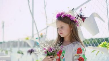 Little amazing girl with blue eyes touches flowers on bright bay bar. 4K