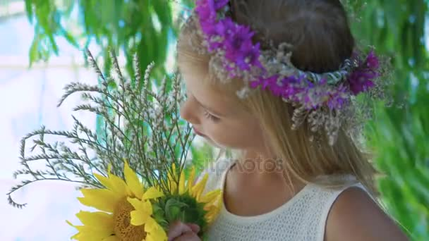 Little blonde with flowers crown and flowers in hands smiles at camera 4K