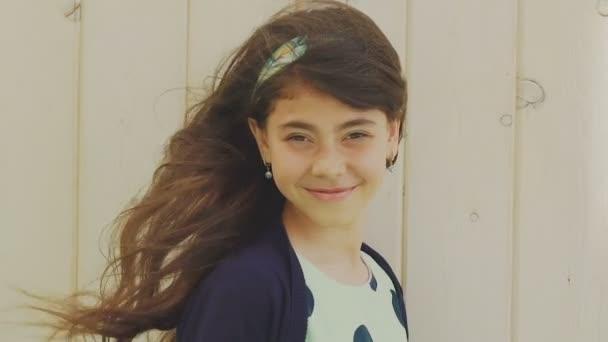Graziosa bruna con gli occhi marroni e capelli lunghi che sorride alla macchina fotografica. Lentamente