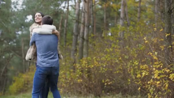 Romantic young couple hug and spin around in a forest. 4K