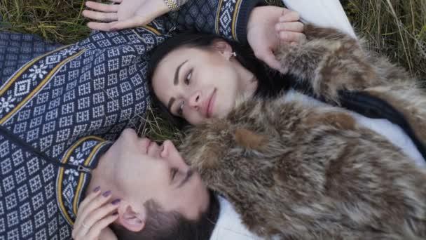 Boldog mosolygó pár pihen a fűben, hazudik. 4k