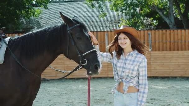 weiblicher Teenager mit freundlichem schwarzen Pferd und lächelnd auf einer Fläche. 4k