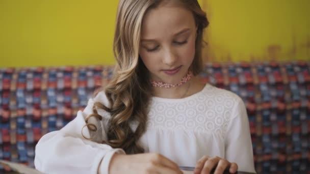 1395dc889f0588 Hübsches, lächelnde junge Mädchen und Lesen der Speisekarte im Café. 4k