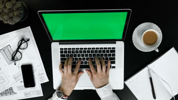 Businessman working at office desk with his laptop with greenscreen.