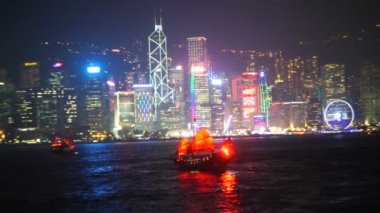 Hong Kong view at night from Victoria harbor with traditional red sail junk boat and modern skyscrapers and other urban buildings of financial district of city