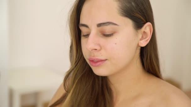 Természet szépség portré fiatal barna kaukázusi nő dönti a fejét, és nézi a kamera szürke háttér. Bőrápolás és természet szépség koncepció