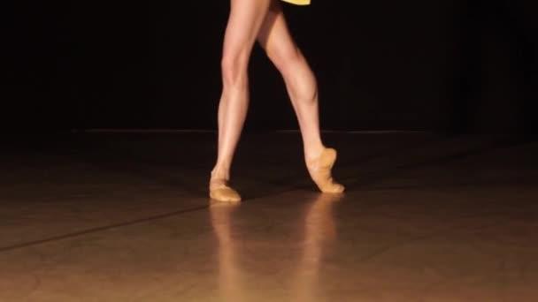 Detailní záběr baletní tanečnice, jak cvičí cvičení na tmavém jevišti nebo studiu. Ženy a muži nohy ve špičatých botách.