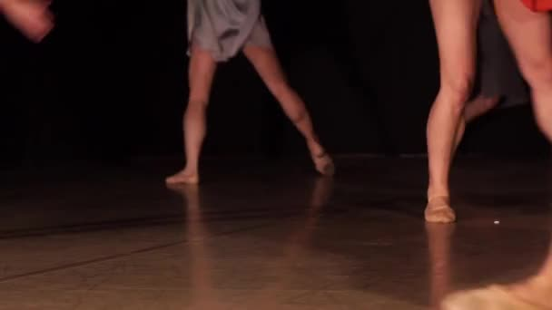 Close up of ballet dancer as she practices exercises on dark stage or studio. Womans and mans feet in pointe shoes.