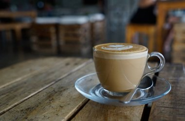 A cup of hot cappuccino on wooden table in a street coffee shop against blurred background. Famous place in Bali Canggu