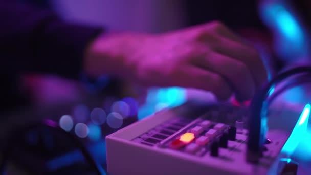 Közelkép a kezekről, ahogy DJ zenél a stúdió műhelyében. A hallgató megtanulja, hogy írjon kreatív hangulatú zenét. Online oktatás. Hangtompító. Színes neon fény