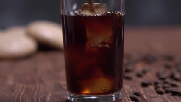 Add hozzá a fekete kávé krém öntjük egy pohár hideg főzött jeges kávé fekete fa asztal kávébab fekete alapon