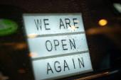 Leuchtkasten mit Schild, hinter einer Glastür des Cafés stehen wir abends bei Regen wieder offen. Wurden nach der Quarantäne wieder geöffnet, Foto des Kleinunternehmensbesitzers. Bitte eine Gesichtsmaske tragen und