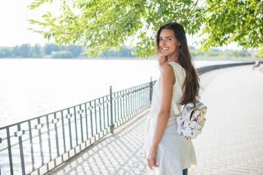 Smiling young woman with backpack, looking from the back, walking in the park with lake. Travel. Vacation