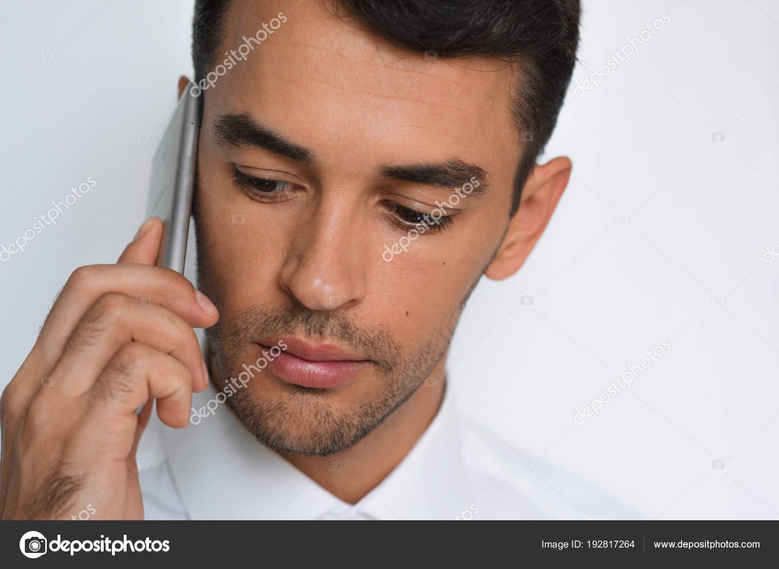 320b3c47136e Bellissimo primo piano ritratto di giovane che per mezzo del telefono  mobile su sfondo grigio. Uomo d'affari che parla sul suo smart phone.