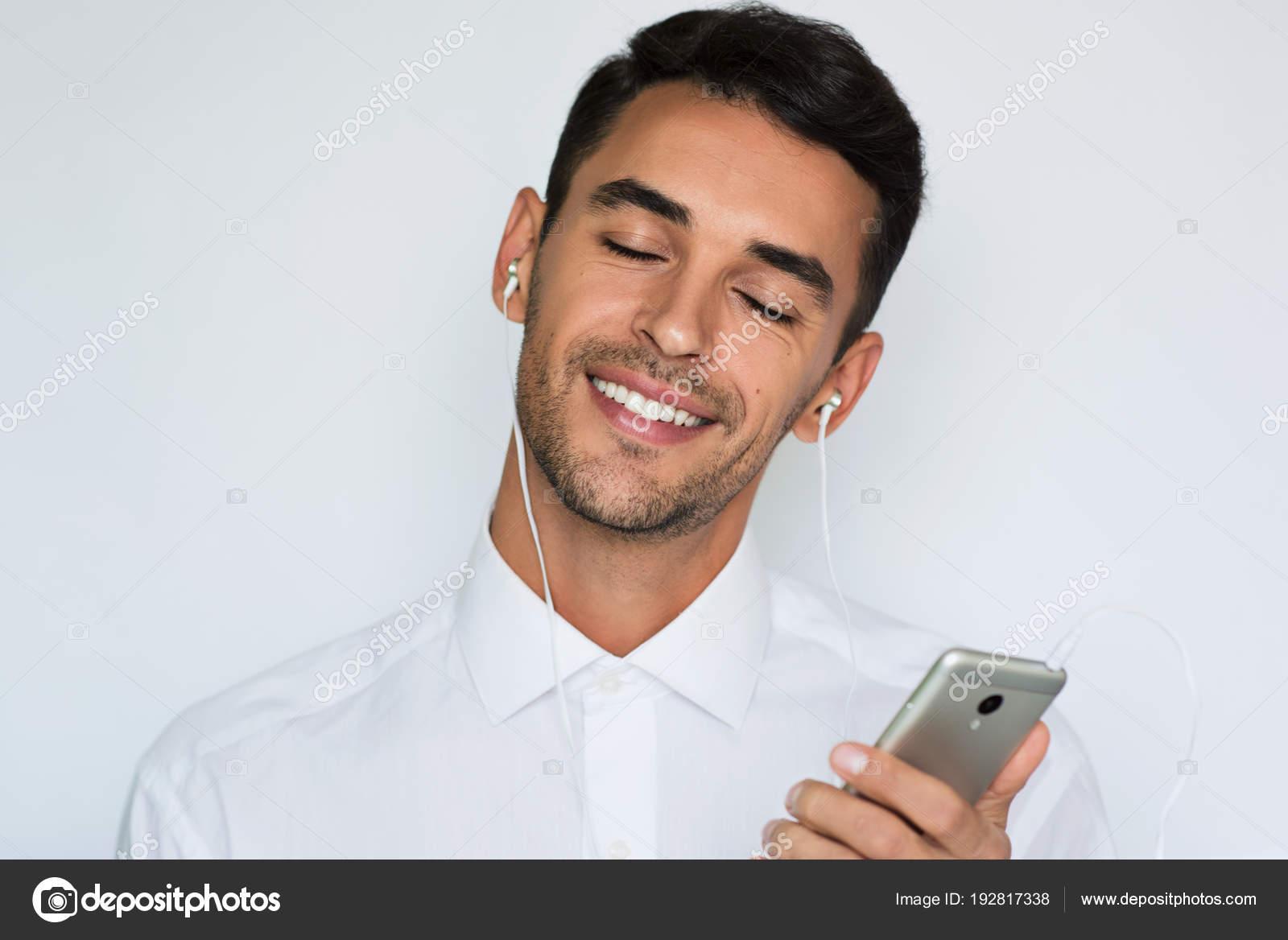 30488f9774c7 Bel ritratto di un uomo bello sorriso attraente giovane in camicia bianca  con i trasduttori auricolari che tiene telefono mobile isolato su sfondo  grigio ...