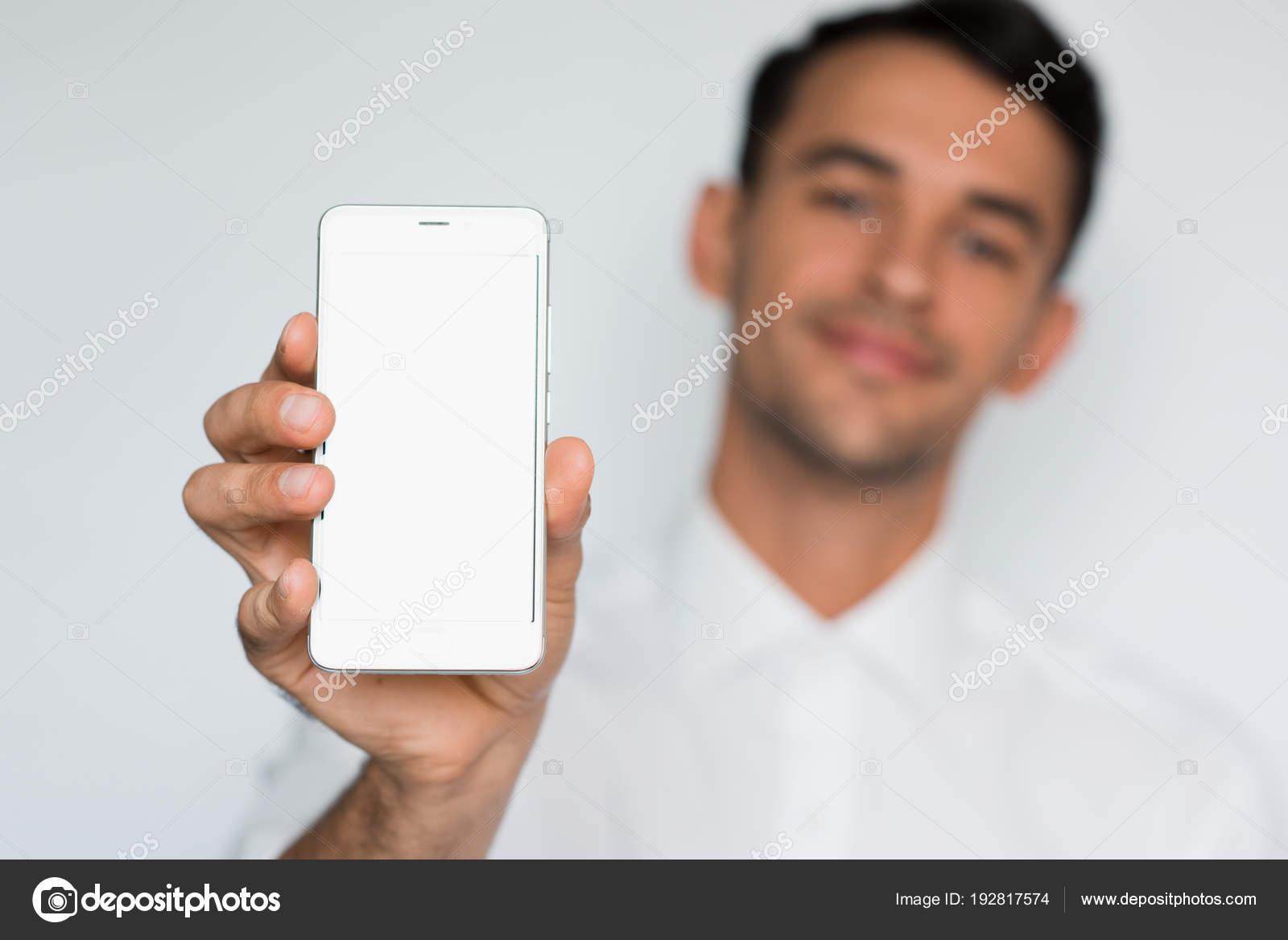 3454bdc61679 Ritratto di giovane uomo bello che mostra uno schermo di telefono astuto in  bianco isolato su uno sfondo grigio ...