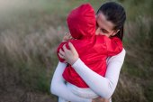 Portrait of beautiful young mother holding her baby toddler wearing red jacket. Happy family, mother and child play cuddling on field walk in nature outdoors.