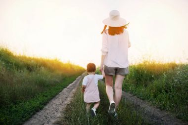 Charming, adorable and amazing view of walking of a pretty mother and beautiful little daughter on a path field. Motherhood and childhood. Sunset or sunrise.