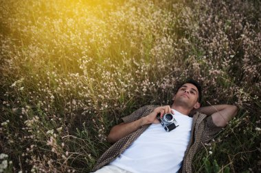Amazing view from above of handsome young man with vintage camera, lying on meadow background. Travel mood. Photography. Relaxation on a field.