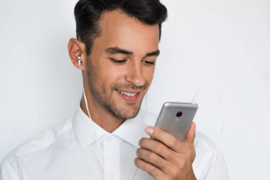 Portrait of a handsome attractive young man in white shirt with earphones holding mobile phone isolated on the light gray background. Happy businessman with smart phone listen trendy concept.