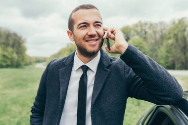 Attractive European caucasian manager in stylish formal coat using mobile phone, near to his car while waiting for colleagues test drive. Stylish happy smiling  businessman have a talk on smart phone.