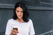 gut aussehende Frau in stylischer Kleidung, liest gute Nachrichten auf dem Handy im Freien, mit High-Speed-Internetverbindung. Teenager-Nachrichten in sozialen Netzwerken. Menschen, Lebensstil und Geschäftskonzept.