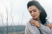 Mladý zasněný žena se zavřenýma očima s rukou na rameni, na sobě šedý svetr. Atraktivní bruneta kavkazské mladá žena s venkovní větrné vlasy. Životní styl módní pojem. Obal nápad.