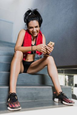 Happy and funny athletic attractive brunette woman with red towel on neck after workout in the gym sits on the stairs and listening the music on earphones from smartphone. Sport concept.