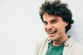 Közelkép egy boldog, jóképű fiatalemberről, aki széleskörűen mosolyog, reklámhoz pózol, mosolyog és a kamerába néz. A göndör hajú, vonzó férfi portréja vidám kifejezéssel bír..