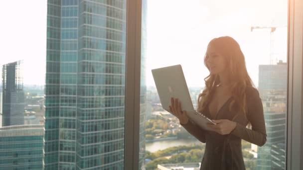 Mladá krásná žena, pohybující se v blízkosti okna a pomocí přenosného počítače na pozadí města,
