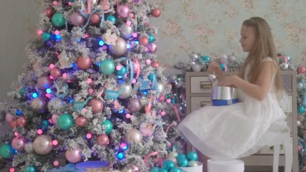 Niedliche kleine Mädchen im weißen Kleid schmücken Weihnachtsbaum zu Hause