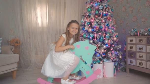 Malá holka sedí na houpací vintage koně poblíž nazdobený vánoční stromeček
