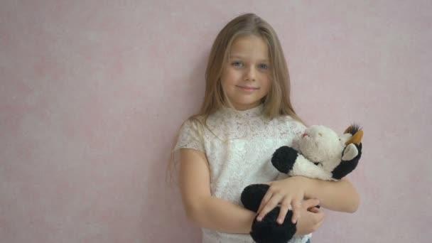 Roztomilá holčička v neformálním oblečení drží Plyšová hračka, při pohledu na fotoaparát a stojící proti růžové pozadí