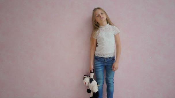 smutný holčička s dlouhými vlasy stojící poblíž růžové zdi s hračkou
