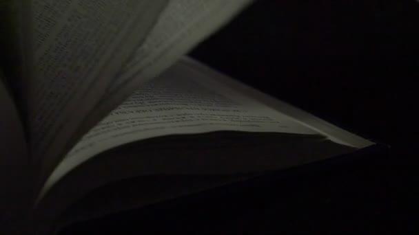 Obracející stránky knihy, na černém pozadí