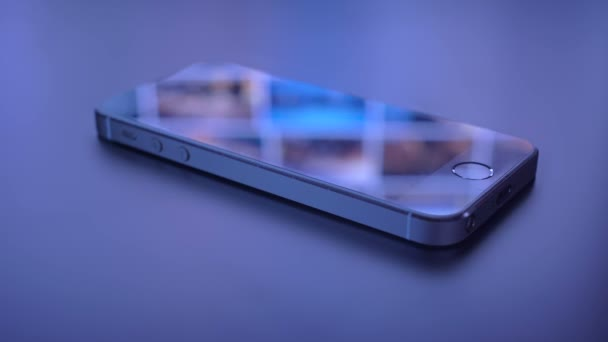 Mobile phone on dark background with reflection. Technology and lifestyle concept.