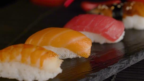 Közelkép a piros pálcika vesz sushi tekercs része a table étterem