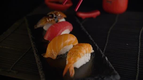 Hand mit roten Essstäbchen, die Sushi nehmen