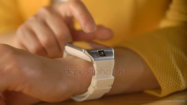 Dámská ruka se dotýká obrazovky chytré hodinky