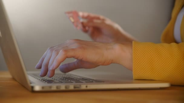 Womans hands holding a credit card and using computer keyboard for online shopping